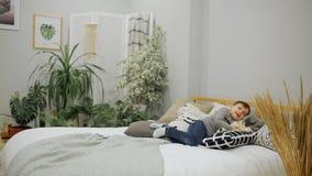 Muchacho 5-7 años en tejanos y un aspecto europeo del suéter gris que salta feliz en la cama en los padres almacen de video