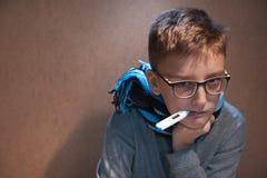 Muchacho 10 años en vidrios con un termómetro en su boca Foto de archivo libre de regalías