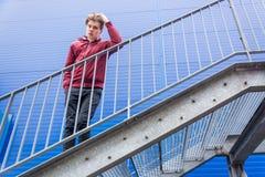 Muchacho aburrido del adolescente que se coloca en las escaleras sobre el edificio azul Imagen de archivo libre de regalías