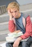 Muchacho aburrido del estudiante con los libros y el ordenador portátil Foto de archivo