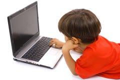 Muchacho aburrido que usa la computadora portátil Fotos de archivo