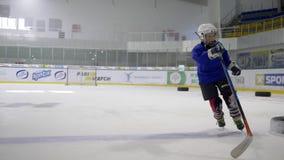 Muchacho activo del niño en casco con la máscara con el palillo de hockey en patín aprender jugar a hockey en campo de hielo almacen de video