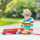Muchacho activo del niño que juega con el autobús escolar y los juguetes rojos Imágenes de archivo libres de regalías