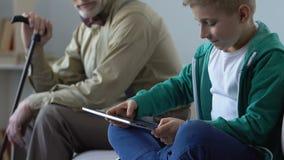 Muchacho adicto que juega al juego de la tableta y abuelo triste que lo mira, condenación metrajes