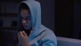 Muchacho adolescente afroamericano que se sienta en la depresión sufridora del sitio oscuro, soledad almacen de video
