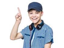 Muchacho adolescente con el casquillo y los auriculares Foto de archivo