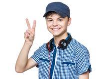 Muchacho adolescente con el casquillo y los auriculares Fotografía de archivo libre de regalías