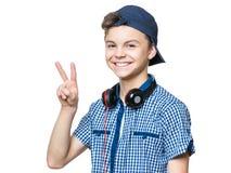 Muchacho adolescente con el casquillo y los auriculares Imagen de archivo