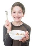 Muchacho adolescente con el cereal de desayuno Foto de archivo