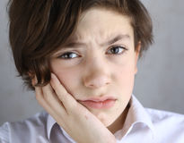 Muchacho adolescente con el dolor de muelas que sostiene su mejilla Imágenes de archivo libres de regalías