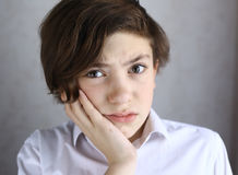Muchacho adolescente con el dolor de muelas que sostiene su mejilla Fotografía de archivo