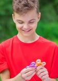 Muchacho adolescente con el juguete del hilandero en parque Imágenes de archivo libres de regalías