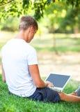 Muchacho adolescente con el ordenador portátil Fotos de archivo