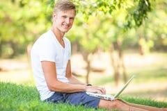 Muchacho adolescente con el ordenador portátil Imagenes de archivo