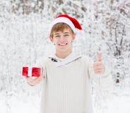 Muchacho adolescente con el sombrero de santa y las cajas de regalo rojas que muestran los pulgares para arriba Foto de archivo