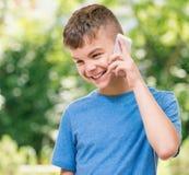 Muchacho adolescente con el teléfono Imágenes de archivo libres de regalías