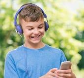 Muchacho adolescente con el teléfono Foto de archivo libre de regalías