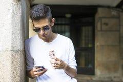 Muchacho adolescente con el teléfono celular al aire libre Foto de archivo