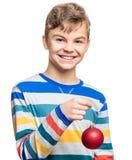 Muchacho adolescente con la bola de la Navidad Imágenes de archivo libres de regalías