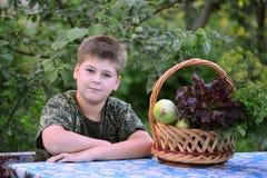 Muchacho adolescente con la cesta de verduras frescas en el jardín Imágenes de archivo libres de regalías