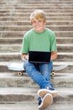 Muchacho adolescente con la computadora portátil Fotos de archivo
