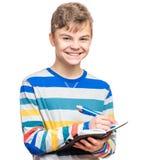 Muchacho adolescente con la escritura de la pluma algo Fotos de archivo libres de regalías