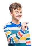 Muchacho adolescente con la escritura de la pluma algo Foto de archivo libre de regalías