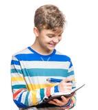 Muchacho adolescente con la escritura de la pluma algo Foto de archivo