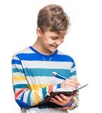 Muchacho adolescente con la escritura de la pluma algo Imagen de archivo