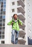 Muchacho adolescente con la mochila que camina en calle de la ciudad Foto de archivo libre de regalías