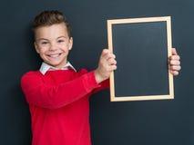 Muchacho adolescente con la pequeña pizarra Imagen de archivo libre de regalías