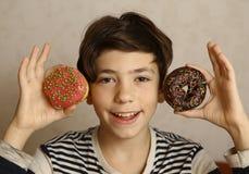 Muchacho adolescente con la sonrisa de los oídos de los buñuelos Imagen de archivo