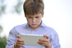 Muchacho adolescente con la tableta en la naturaleza Fotos de archivo libres de regalías