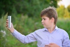 Muchacho adolescente con la tableta en la naturaleza Imagen de archivo libre de regalías