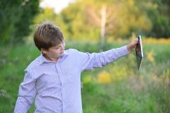 Muchacho adolescente con la tableta en la naturaleza Fotografía de archivo