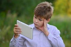 Muchacho adolescente con la tableta en la naturaleza Imágenes de archivo libres de regalías
