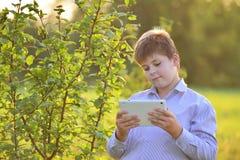 Muchacho adolescente con la tableta en la naturaleza Fotografía de archivo libre de regalías