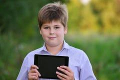 Muchacho adolescente con la tableta en la naturaleza Imagenes de archivo