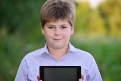 Muchacho adolescente con la tableta en la naturaleza Imagen de archivo