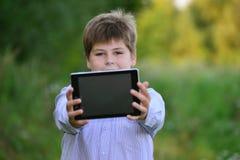 Muchacho adolescente con la tableta en la naturaleza Foto de archivo libre de regalías
