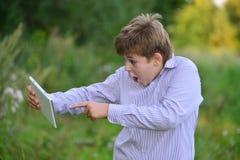 Muchacho adolescente con la tableta en la naturaleza Foto de archivo