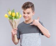 Muchacho adolescente con las flores Fotografía de archivo libre de regalías