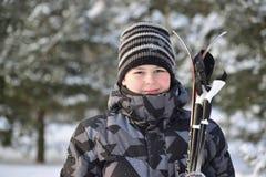 Muchacho adolescente con los esquís en un bosque del pino en invierno Fotos de archivo