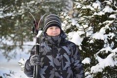Muchacho adolescente con los esquís en un bosque del pino en invierno Fotografía de archivo libre de regalías
