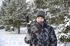 Muchacho adolescente con los esquís en un bosque del pino en invierno Foto de archivo libre de regalías