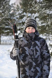 Muchacho adolescente con los esquís en un bosque del pino en invierno Fotos de archivo libres de regalías