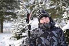 Muchacho adolescente con los esquís en un bosque del pino en invierno Fotografía de archivo