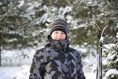 Muchacho adolescente con los esquís en un bosque del pino en invierno Imágenes de archivo libres de regalías
