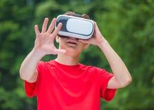 Muchacho adolescente con los vidrios de VR en parque Imágenes de archivo libres de regalías