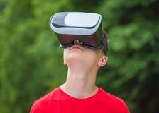 Muchacho adolescente con los vidrios de VR en parque Fotografía de archivo libre de regalías